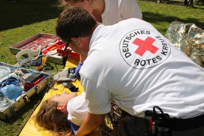 Helfer des Bayerischen Roten Kreuzes versorgen eine verletzte Person.