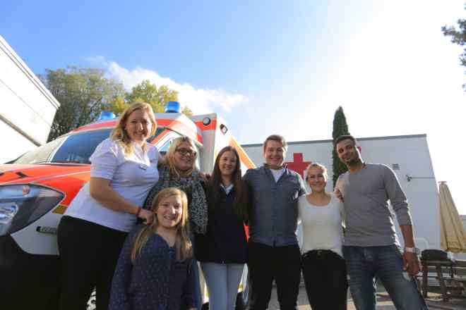 Teilnehmer des Rotkreuzkurses Erste-Hilfe-Ausbildung vor einem RTW