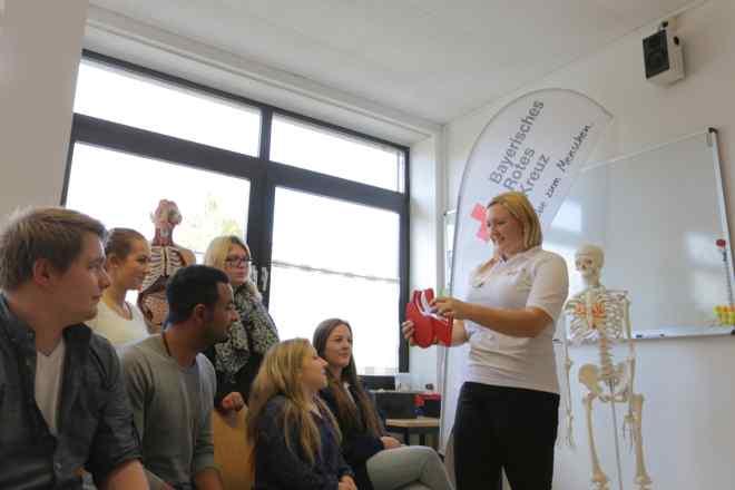 Ausbilderin erklärt den Teilnehmern des Rotkreuzkurses am Modell die Gefahren der Bewusstlosigkeit.