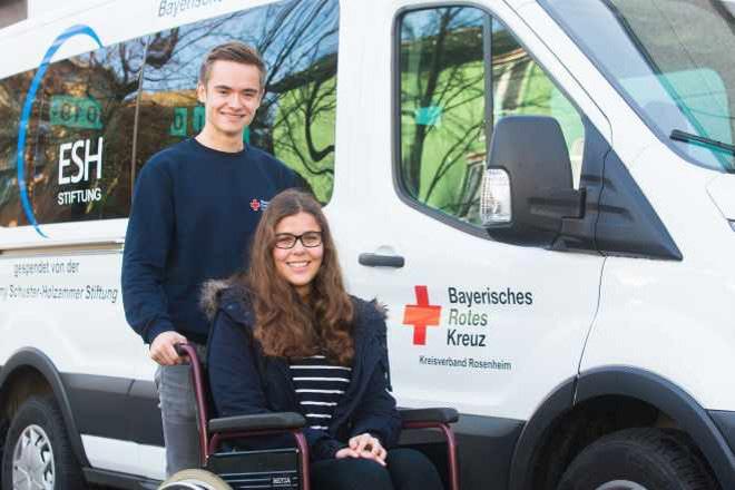 das Foto zeigt jungen BFD-Mitarbeiter mit Mädchen im Rollstuhl
