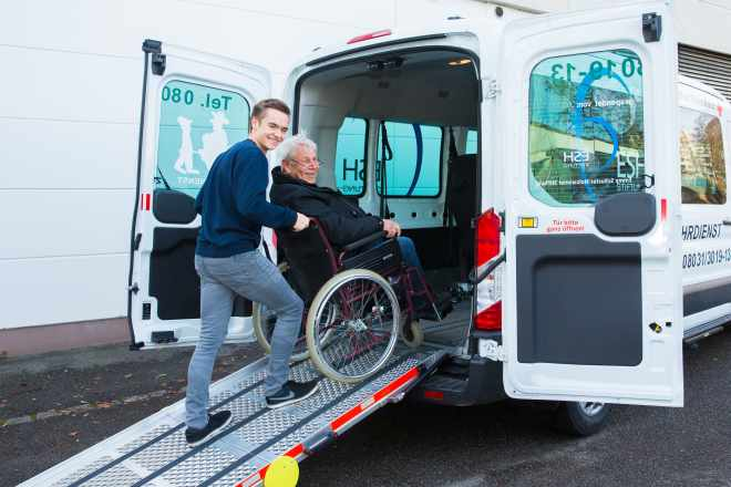 das Foto zeigt einen BRK Mitarbeiter, der einen älteren Mann im Rollstuhl über eine Rampe in das Fahrzeug schiebt.