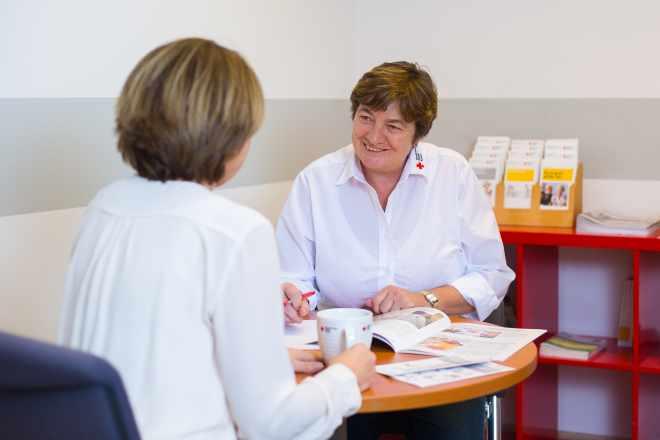das Foto zeigt eine Mitarbeiterin des BRK Pflegedienstes bei einem Beratungsgespräch mit einer Angehörigen.