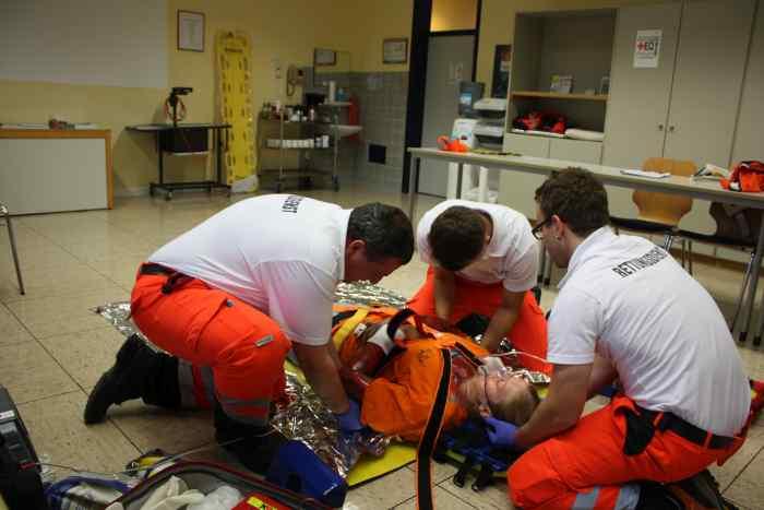 3 Sanitäter des Roten Kreuzes haben im Schulungsraum einen Notfalldarsteller mit einem Spine Board fixiert.