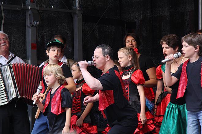 das Foto zeigt eine Gruppe behinderter und nicht behinderter Menschen bei einem Gesangsauftritt