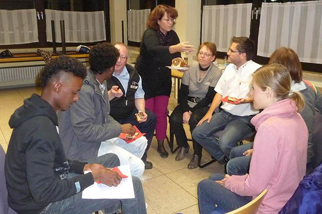 das Foto zeigt Rotkreuzmitarbeiter und junge Flüchtlinge im Stuhlkreis bei einer Veranstaltung
