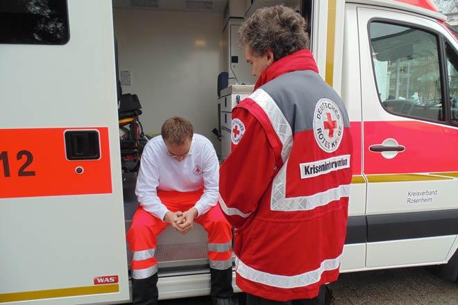 Ein Mitarbeiter des Kriseninterventionsteams betreut einen Mitarbeiter des Rettungsdienstes.