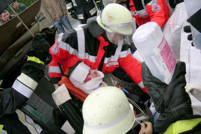 Helfer des Roten Kreuzes versorgen Zusammen mit der Feuerwehr einen Schwerverletzten, der in einem PKW eingeklemmt ist. Das Bild entstand während einer Übung.