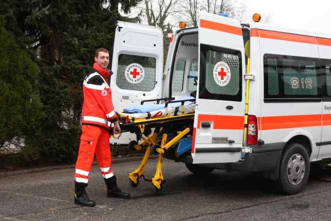 das Bild zeigt Rotkreuzmitarbeiter mit Trage am Krankenwagen