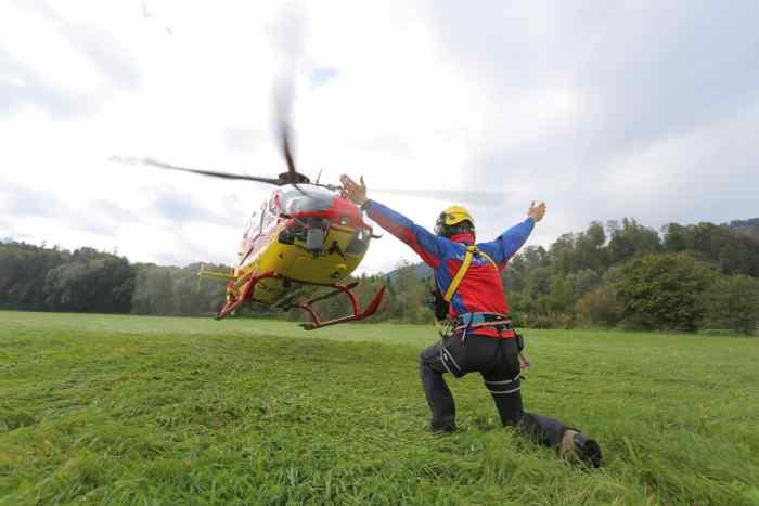 Mitglied der Bergwacht weist Rettungshubschrauber ein