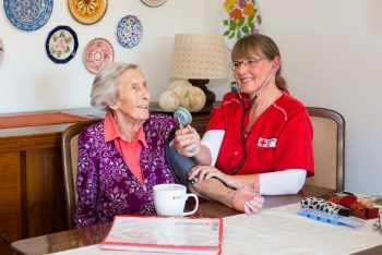 Foto zeigt Pflegeschwester, die bei Patientin Blutdruck misst