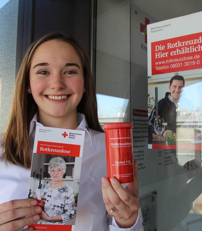 Rotkreuzmitarbeiterin mit Rotkreuzdose und Infoflyer vor Plakat