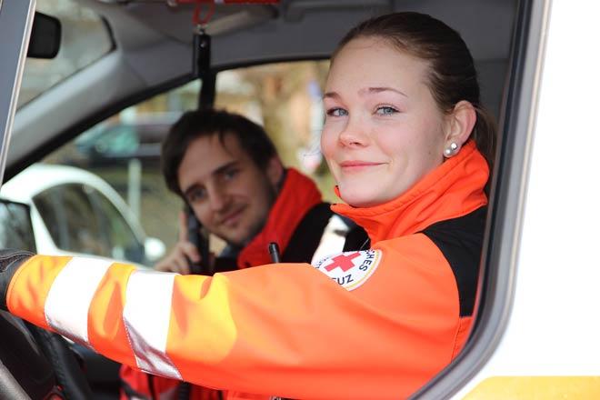 Foto zeigt junge Frau und jungen Mann in Rettungsdienstbekleidung in Rettungswagen