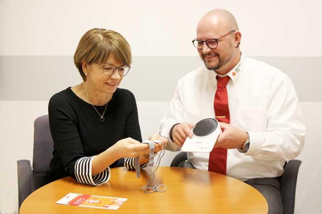 Bild zeigt Mitarbeiter des Roten Kreuzes, der gerade einer Kunden das Alarm-Armband des Hausnotrufes anlegt und die Funktion erklärt.