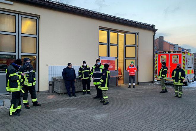 Foto zeigt Mitglieder der Feuerwehr und des BRK, die zur Testung bereit stehen