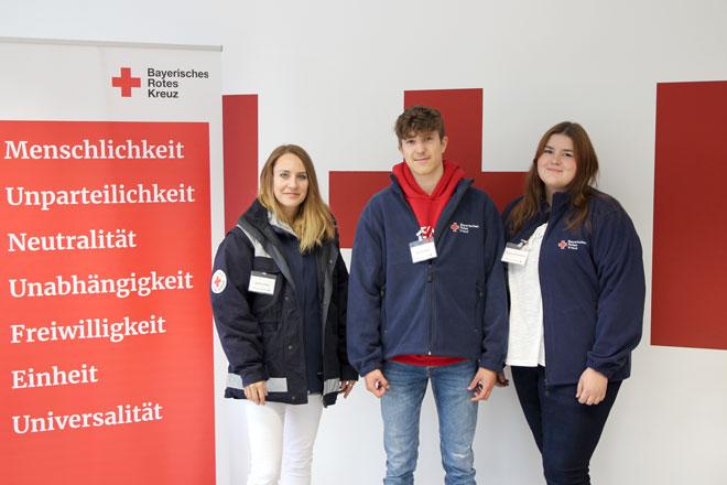 Das Foto zeigt zwei junge Frauen und einen jungen Mann in Rotkreuz-Kleidung
