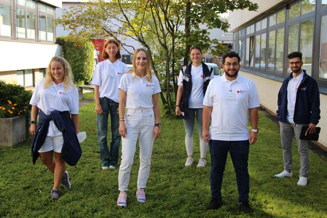 Foto zeigt einige junge Männer und Frauen in Rotkreuz-Kleidung