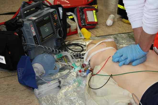 Bild zeigt Mitarbeiter bei der Herz-Lungen-Wiederbelebung an einer Übungspuppe. Angeschlossen sind ein Defibrillator und ein Beatmungsbeutel.