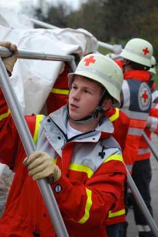 Das Bild zeigt einen Jungen in Rot-Kreuz-Kleidung.