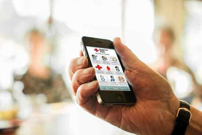 Eine Hand hält ein Smartphone. Dabei ist die Rotkreuz-App geöffnet.
