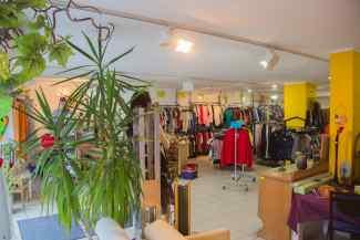 Das Bild zeigt die Ladeneinrichtung des Kleiderladen Kolbermoor mit Kleidung, Möbrltücken und der Kassentheke.