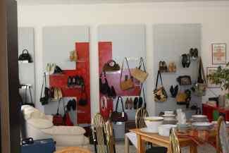 Das Bild zeigt das BRK-Logo. Darüber sind an der Wand Schuhe und Taschen. Im Vordergrund ein Tisch.