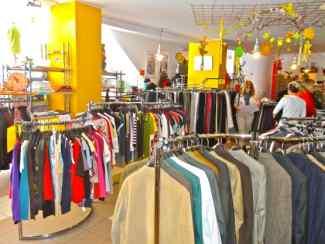 Das Bild zeigt den Kleiderladen Rosenheim von innen. Zu sehen sind viele Kleidungsstücke an Kleiderständern.