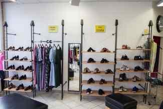 Das Bild zeigt ein Schuhregal und das Logo des BRk im Kleiderladen Bad Endorf.
