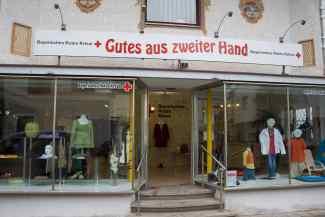 """das Bild zeigt drei Stufen, die zum Eingang des Kleiderladens führen. Außerden das Schaufenster und das Logo ,,Gutes aus zweiter Hand""""."""