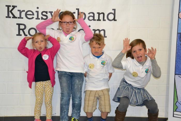 das Foto zeigt vier Kinder vor einem JRK Plakat, die vor Freude hochspringen.