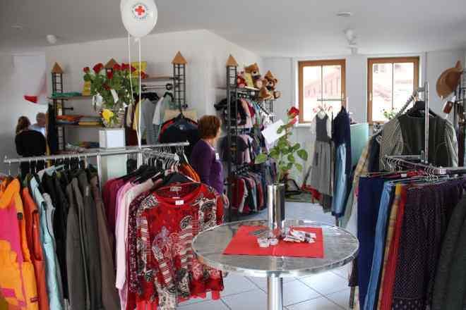 Das Bild zeigt einen Stehtisch, Schaufensterpuppen und Kleidung.