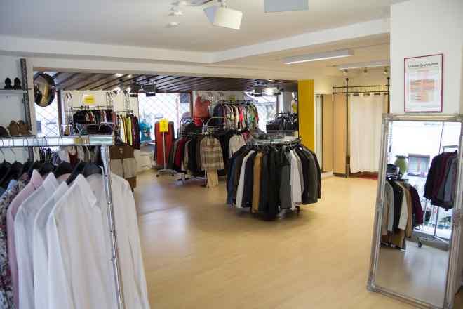 Das Bild zeigt Kleiderständer mit Kleidung und die Umziehkabine.