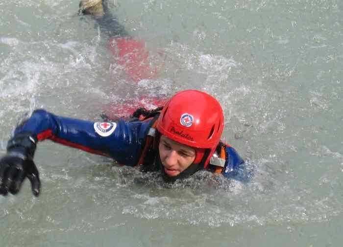 Das Bild zeigt einen Wasserretter der Wasserwacht Rosenheim bei einem Einsatz im Fließgewässer